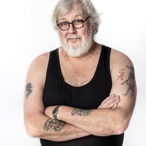 Lauri Vuorinen esittelee tatuointejaan studiokuvassa.