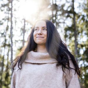 Säde-Tuulia Sällylä katsoo ohi kamerasta auringon paistaessa takana olevien puiden takaa.