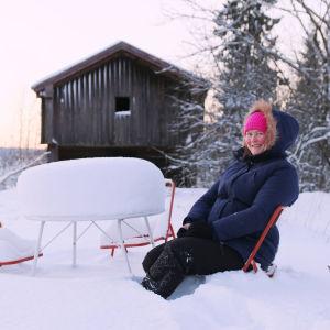 En glad kvinna sitter på en sparkstötting i djup snö.