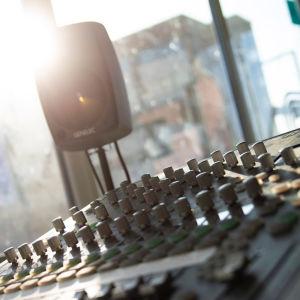 Radion äänimikserin nappuloita, aurinko paistaa ikkunasta sisään studioon.