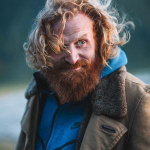 Kristofer Hivju utomhus med vind i håret och finurlig min.