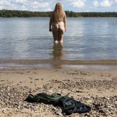 Roosa Vastamäki on kahlannut melkein polvien syvyyteen merelle. Rantahiekalla on hänen musta-vihreät rintaliivinsä.