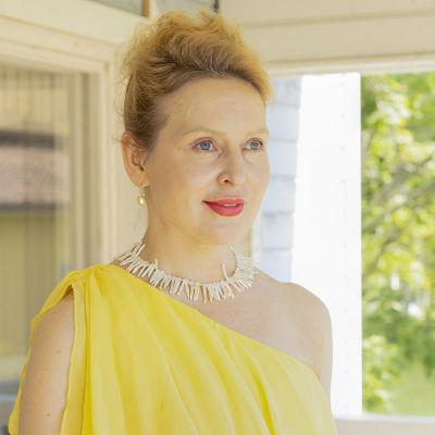 Opperalaulaja Marie Finne-Bray katsoo aurinkoisella kuistilla kameran ohi.