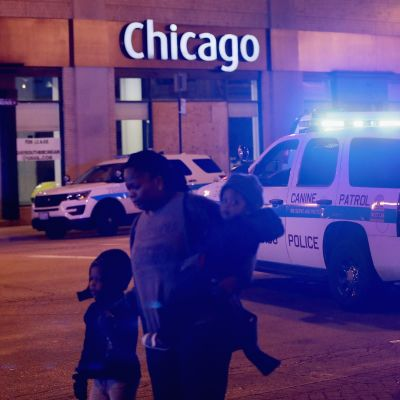 En mamma med tre barn avlägsnar sig från platsen för en masskjutning i Chicago, medan en polis dirigerar.