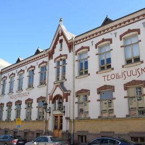 Skolbyggnaden på Smedsgatan 2. Den har en vit fasad med röda tegeldekorationer på fönstren.