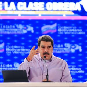 Maduro puhuu ja vahvistaa sanojaan kohottamalla oikeaa kättään. Hänellä on yllään vaalea kauluspaita. Hänen edessään pöydällä on mikrofoni ja näyttö. Taustakangas on sininen.