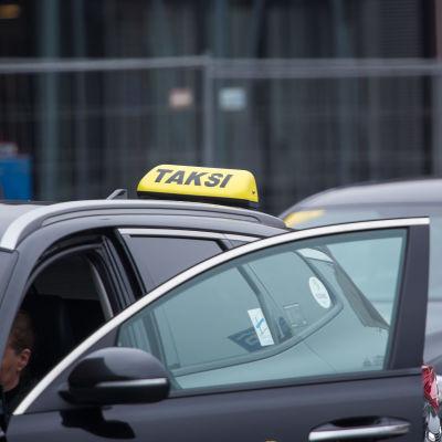 Två taxibilar står och väntar på nya kunder.