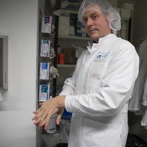 Timo Huovinen pesee käsiään lääkevalmistaja Finvectorin laboratorion aulassa.