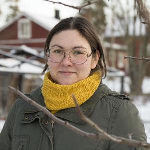 En kvinna iklädd gul halsduk och grön jacka. I bakgrunden syns ett rött gammalt hus. Det är vinter och snö på marken.