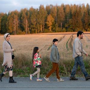 Familjen Mehdipour på promenad mot bakgrunden av en finländsk åker i solnedgången.
