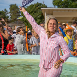 En kvinna i rosa pyjamas står mitt i en vattenfylld fontän. Hon skrattar och vinkar!