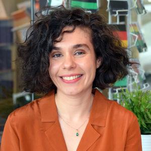 Kvinna i orange tröja och brunt hår ler stort mot kameran.