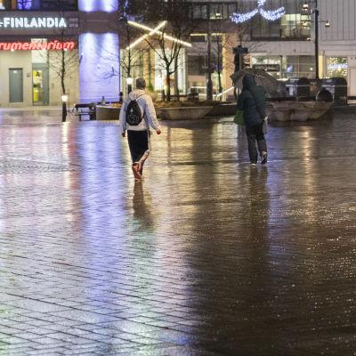 Ihmisiä kävelemässä sateisella Kuopion torilla.