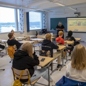En lärare med munskydd står framför ett klassrum fullt av elever.