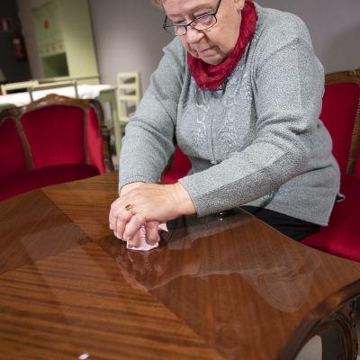 Suonenjokinen Pirkko Hytönen näyttää miten huonekaluja kiillotettiin Kutvosen huonekalutehtaalla.
