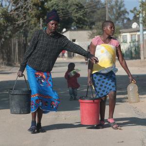 Två kvinnor bär på vattenämbare.