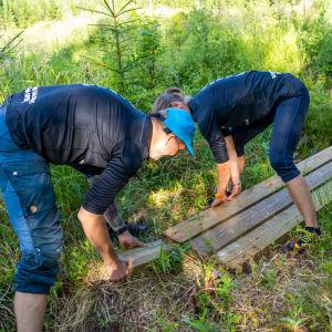 Två personer bygger spång.