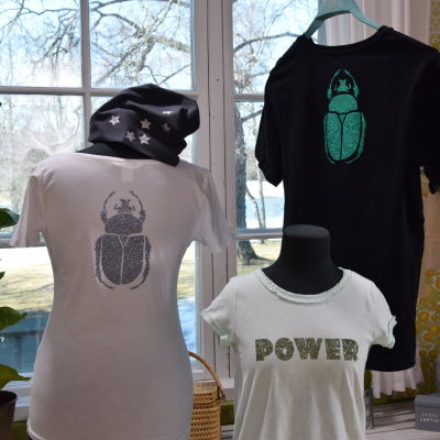tre t-tröjor med glittermönster framför ett fönster