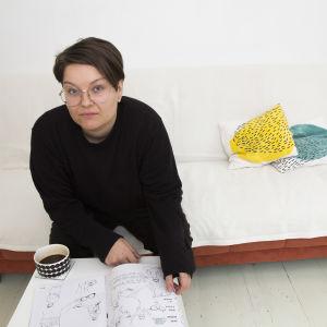 Zarah Holmberg sitter i en soffa och läser i tidningen hen gjort. Hen tittar in i kameran.
