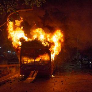 En av de många bussar som demonstranter brände upp under bråken på fredag kväll i Santiago.