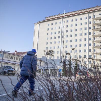 Ihminen kävelee kohti Pohjois-Karjalan keskussairaalan päärakennusta.
