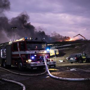 Släckningsarbete på avstjälpningsplatsen. I förgrunden en brandbil mot en lilaskimrande himmel.