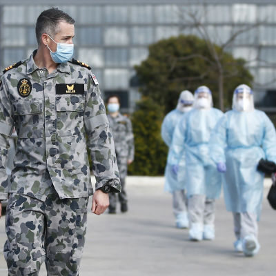 Sotilas kävelee maastopuvussa hoitajien edellä