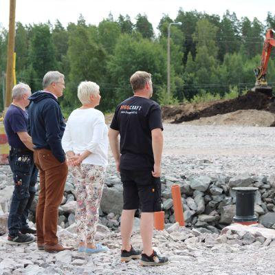 Fyra personer står på ett område och tittar på en gräsmaskin som arbetar.