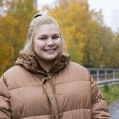 En blond kvinna iklädd en tjock beige dunjacka. Hon ler. I bakgrunden syns träd med gula höstlöv.