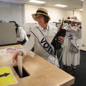 En kvinna lägger en valsedel i en valurna.