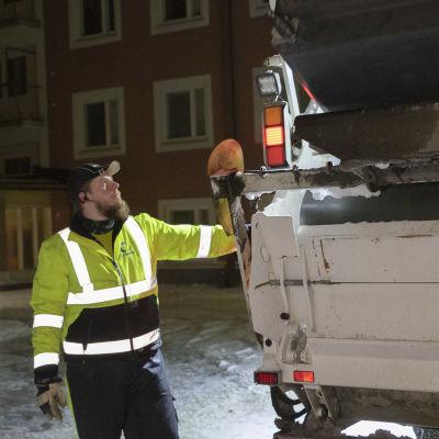 Jäteautonkuljettaja Miikka Kesonen tyhjentää roska-astiaa jäteautoon.