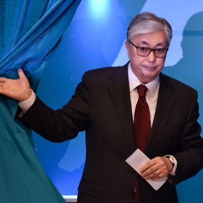 Kassym-Jomart Tokayev stiger fram bakom ett blått draperi.
