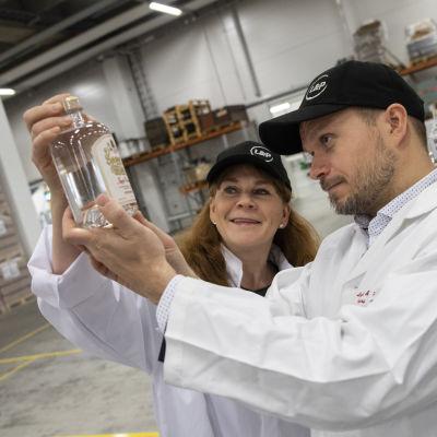 Lignell & Piisapsen toimitusjohtaja Kirsi Räikkönen ja kehitysjohtaja Harri Nylund katselevat viinapulloa.