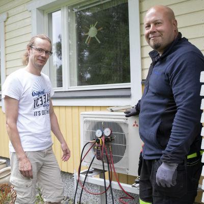 Kimmo Kostamo ja kylmälaiteasentaja Antti Varis seisovat Kostamon takapihalla ilmalämpöpumpun vieressä.