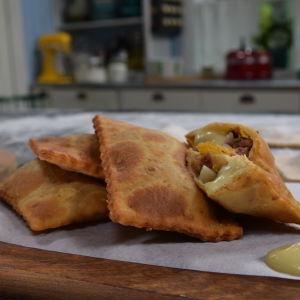 Friterade piroger med äppeldipp på en skärbräda i ett kök