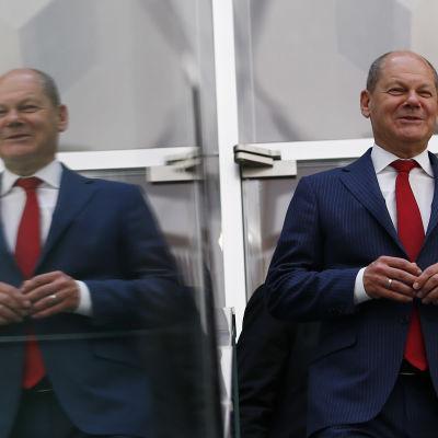 Olaf Scholz kävelee heijastavan lasin ohi, vasemmalla näkyy peilikuva
