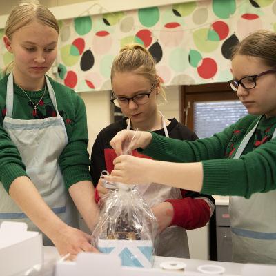 Kuopiolaisen Neulamäen koulun oppilaat Elsa Haatainen, Olivia Renkas, Saimi Tuhkanen pakkaavat piparkakkutaloa pakettiin.
