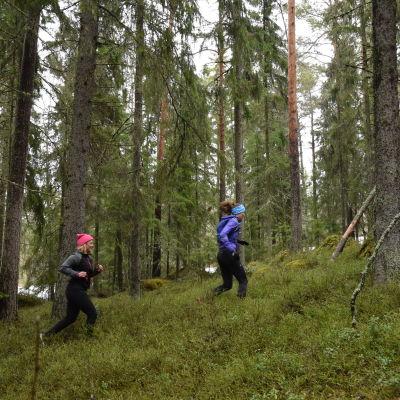 Elin Skagersten-Ström ja Ida Kronholm juoksevat metsässä.