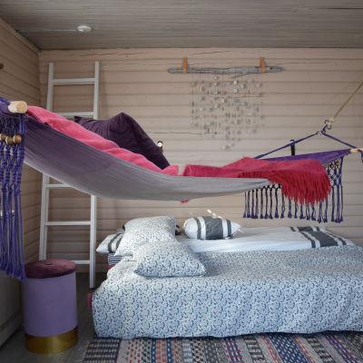 Huone jossa on sänky ja riippumatto