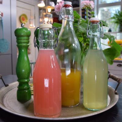 Kolme erilaista alkoholitonta vaihtoehtoa ruokajuomille lasipulloissa keittiössä.