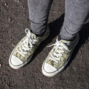 Vader och fötter sedda uppifrån. Fötterna är i tennisskor och underlaget är mörkt grus.