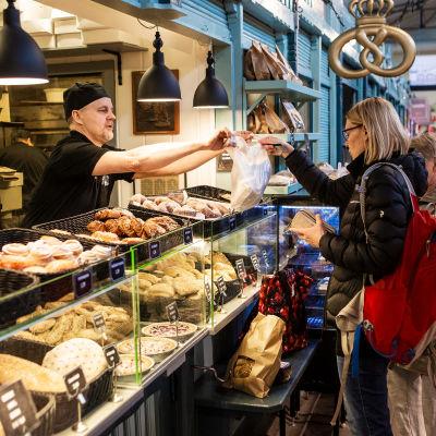 Kauppahallin Leipomon Tapani Ojala ojentaa asiakkaalle leipomo-ostokset mukaan ennen vappua huhtikuussa 2020.