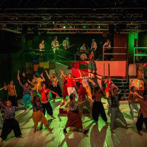 Ungdomar på scen dansar i indiska kläder.