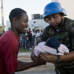 Bolivisk FN-soldat överlämnar spädbarn till dess far.