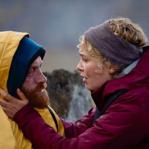 Erik i gul regnrock utmatad och frusen med Ingrid som håller om hans kinder ute på stranden.