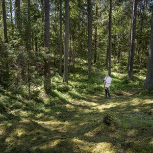Ritva Kovalainen står mitt i en barrskog.
