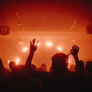 Personer dansar med ryggen mot kameran i ett rött ljus i ett dunkelt rum. Personen närmast kameran håller upp sina händer mot taket.