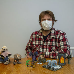 En man sitter vid ett bord. På bordet har han radat upp flera små miniatyrfigurer i plast som föreställer troll och andra fantasifigurer.