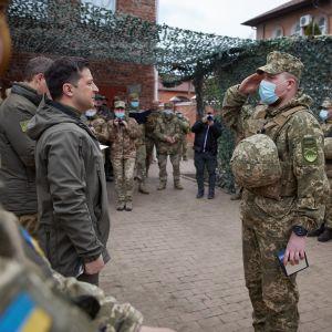Ukrainas president Volodomyr Zelenskyj står tillsammans med en grupp soldater framför honom står en soldat i ansiktmask som gör honnör.