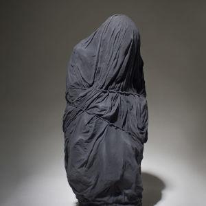 Tiia Matikaisen teos Nobody. Teoksessa istuva ihminen on kääritty mustaan kaapuun. Edes silmiä ei näy.